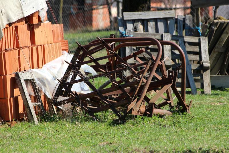 Abandoned vintage retro rusted agricultural farming equipment used to work with tractors on soil left in backyard surrounded with. Uncut grass and construction royalty free stock photos