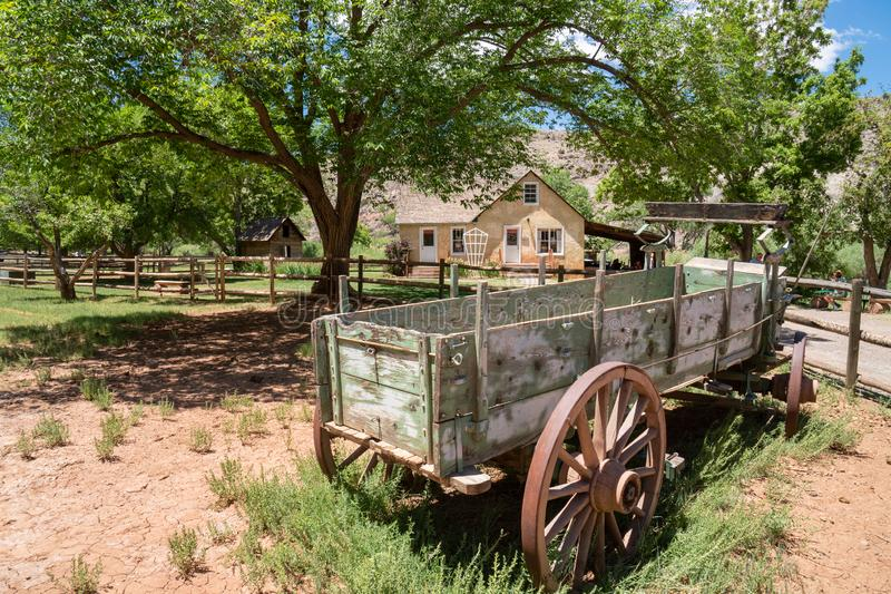 Abandoned wagon sits in a grassy spot in Fruitia Utah, a public orchard in Canyonlands National Park in Utah stock photo