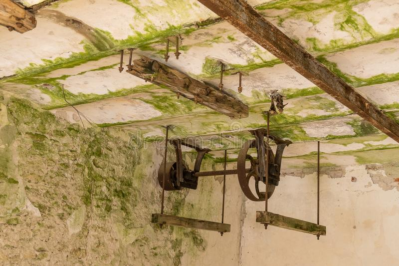 Abandoned water mill. Rusty wheels and green moss covered the old brick wall royalty free stock photography