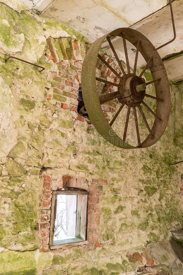 Abandoned water mill. Rusty wheels and green moss covered the old brick wall stock image