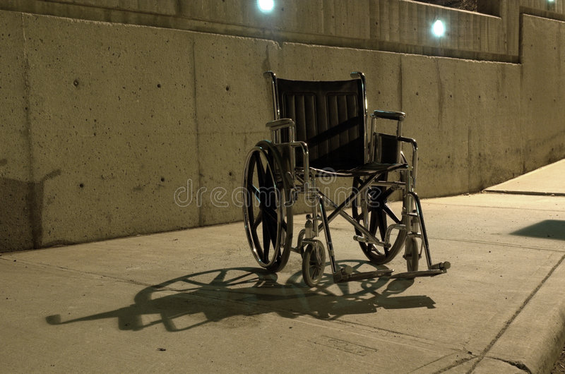 Abandoned wheel chair. At a hospital at night stock photography