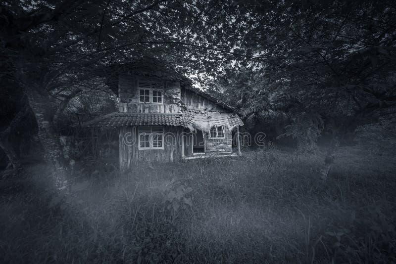Abandoned wood house looks haunted. Image of abandoned wood house looks haunted with damaged rooftop. Shot at night time stock photo