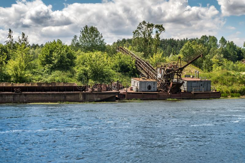 Abandoned wreck of old rusty boat half submerged in the river stock images
