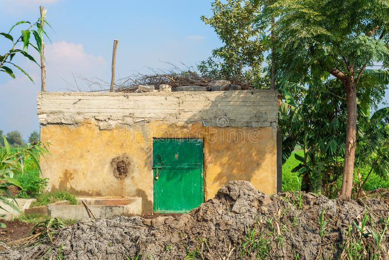 Abandoned yellow rocked hut with single green wooden door, tropical green trees and lots of clay stock image