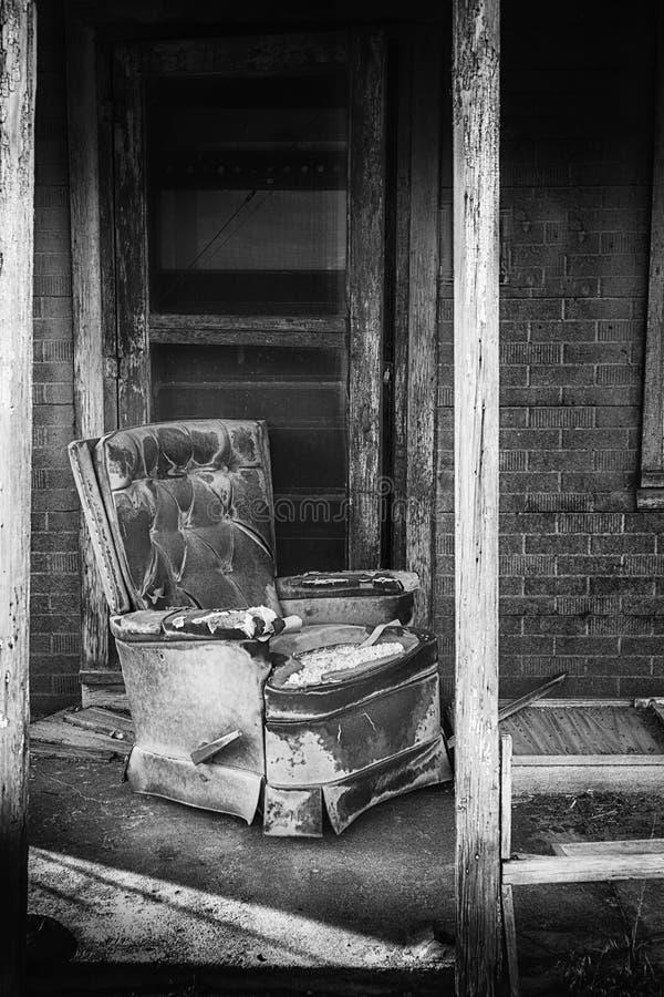 Abandonné à la maison avec un porche et une chaise photo libre de droits