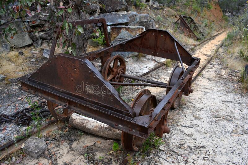 An abandoned mining trolley sits on tracks near a disused mine in Australia stock photos