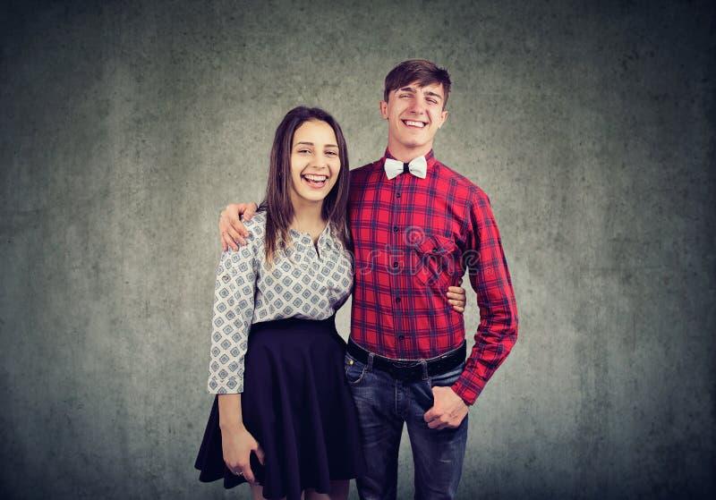 Abarcamiento alegre uno otro de la mujer joven y del hombre, el mirar y sonrisa la cámara imágenes de archivo libres de regalías