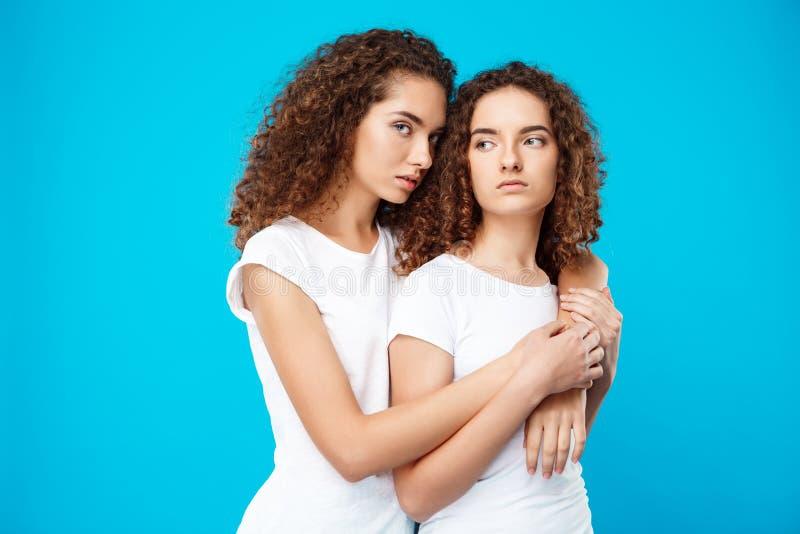 Abarcamiento de dos gemelos de las muchachas, mirando la cámara sobre fondo azul imágenes de archivo libres de regalías