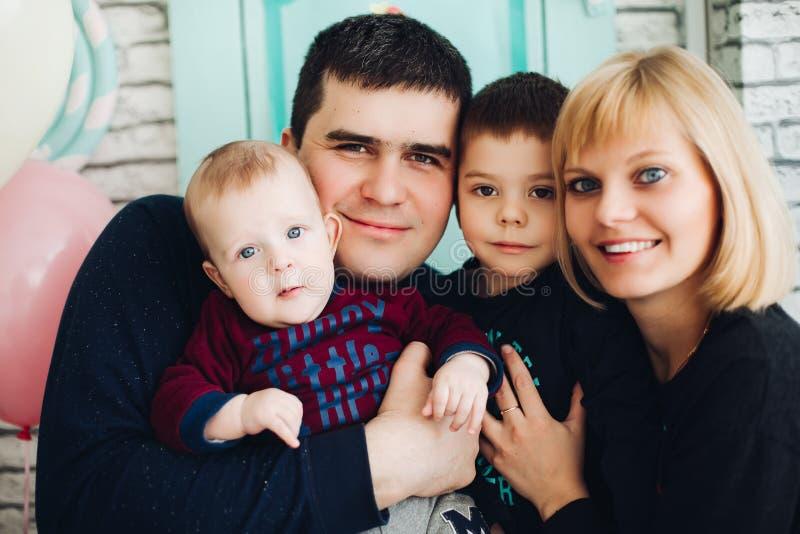Abarcamiento feliz de la familia, de la madre, del padre y de dos pequeño hijos imágenes de archivo libres de regalías