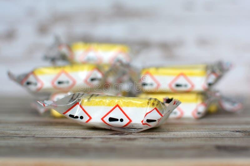 Abas seladas amarelas da limpeza do detergente para a roupa ou da máquina de lavar louça com etiqueta de advertência no pacote imagem de stock royalty free