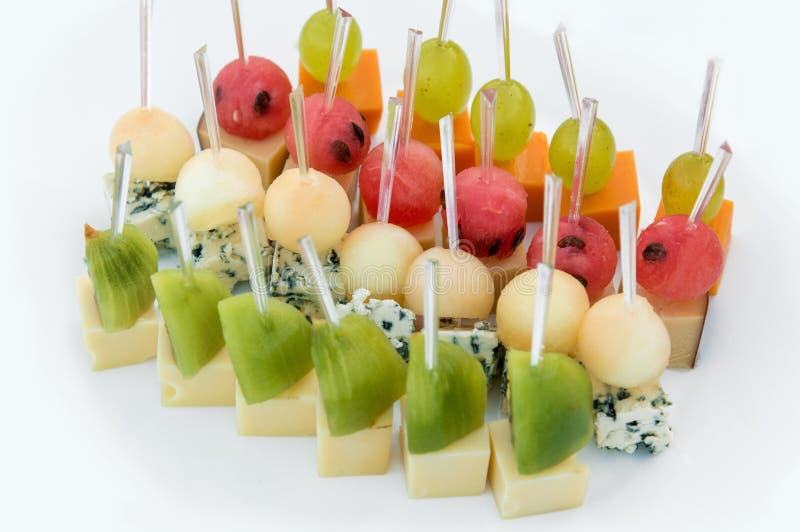 Abastecimiento del partido Ciérrese para arriba de los aperitivos con la sandía, uvas, melón, kiwi, Cheddar, parmesano, queso ver imágenes de archivo libres de regalías