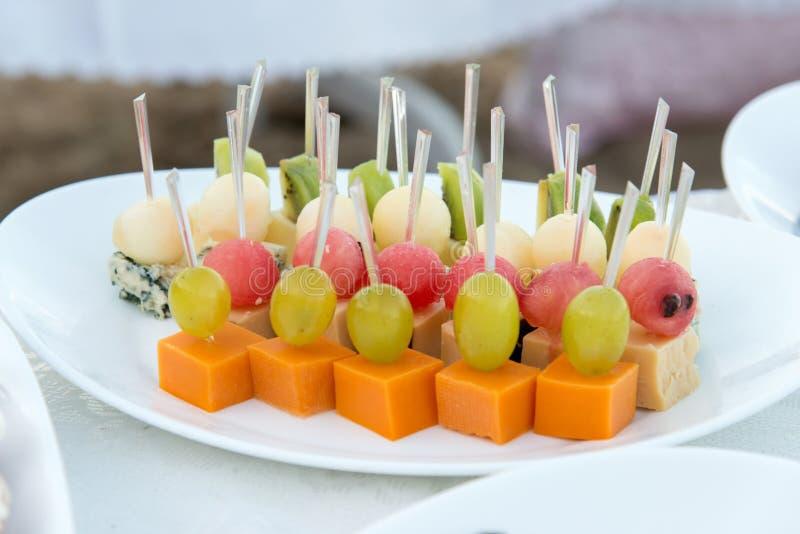 Abastecimiento del partido Ciérrese para arriba de los aperitivos con la sandía, uvas, melón, kiwi, Cheddar, parmesano, queso ver imagen de archivo
