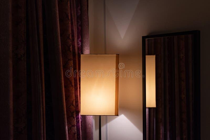 Abat-jour de forme rectangulaire près de miroir encadré sur le mur de la pièce avec les rideaux fleuris en couleur de Bourgogne images libres de droits