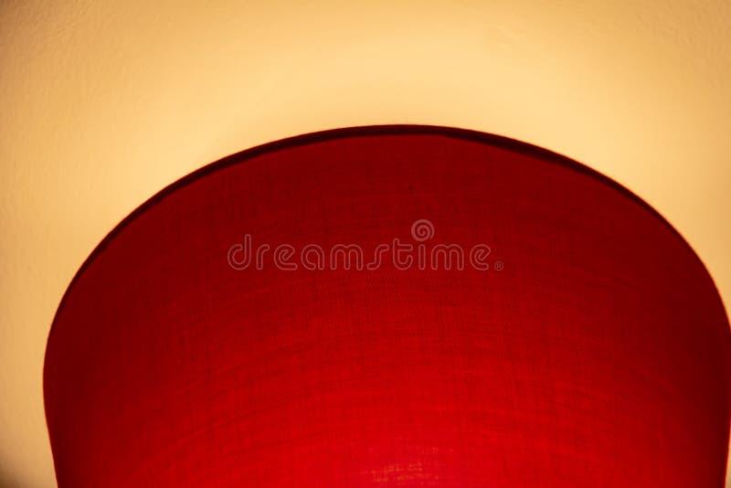 Abat-jour rouge contre un plafond jaune image stock
