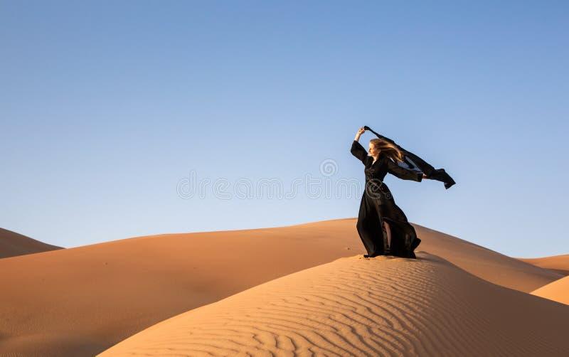 abaya的夫人在沙丘 免版税库存图片