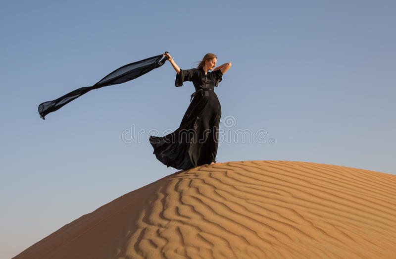 abaya的夫人在沙丘 免版税库存照片