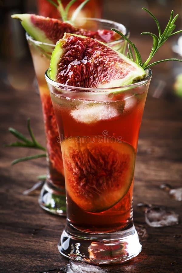 Abb. roter Cocktail mit Cognac, Likor, Kalksaft, Feigen und Honig, alter Holztisch, Barwerkzeuge, Kopierraum lizenzfreies stockbild