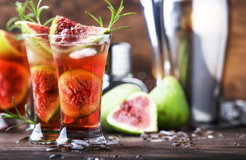 Abb. roter Cocktail mit Cognac, Likor, Kalksaft, Feigen und Honig, alter Holztisch, Barwerkzeuge, Kopierraum lizenzfreie stockfotos