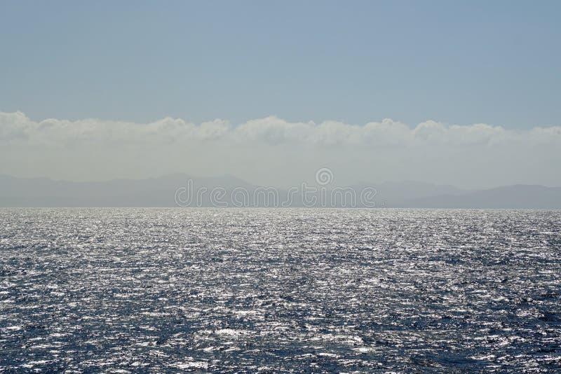 Abbagliamento luminoso di abbagliamento e di giorno soleggiato sulla superficie dell'oceano immagini stock