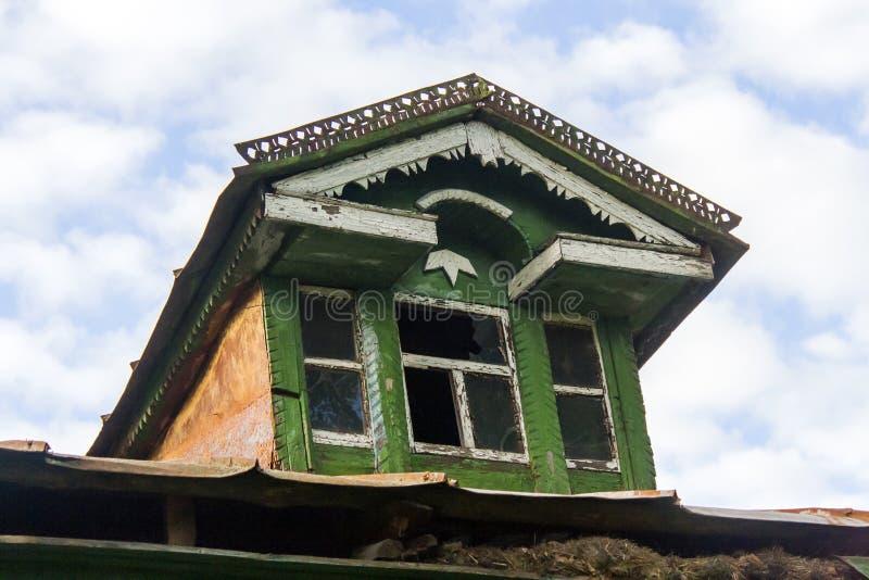 Abbaino decrepito sul tetto di una capanna russa di legno immagini stock