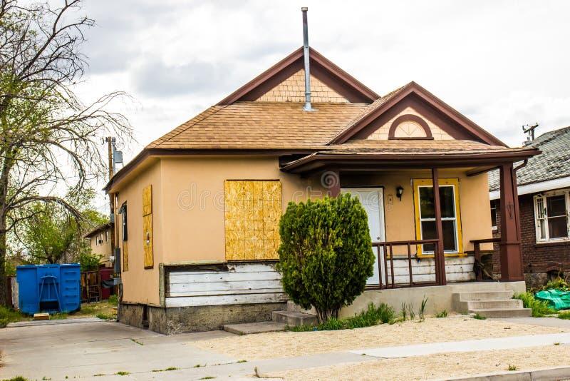 Abbandonato una casa livellata con imbarcato su Windows fotografia stock