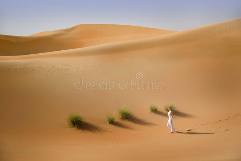 Abbandoni, dune di sabbia, passeggiate della donna vestite bianco immagine stock
