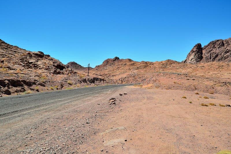 Abbandoni il paesaggio, montagne dell'arenaria rossa, una pianura coperta di vegetazione rara del deserto, un tratto della strada fotografia stock