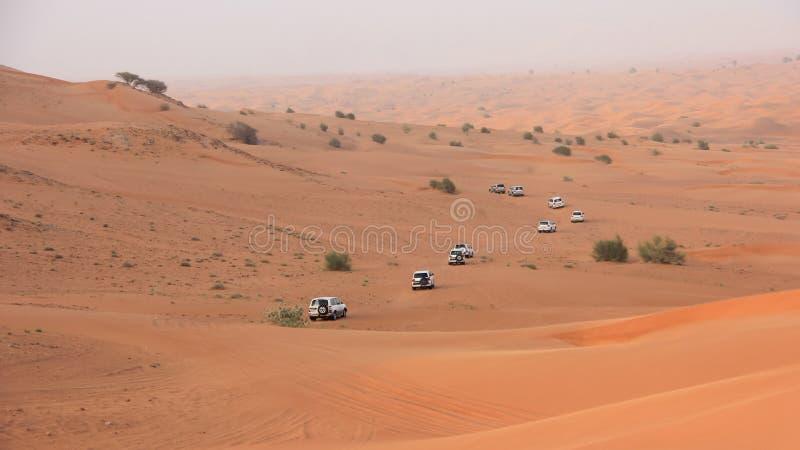 Abbandoni il safari SUVs che colpisce attraverso le dune di sabbia arabe fotografia stock libera da diritti