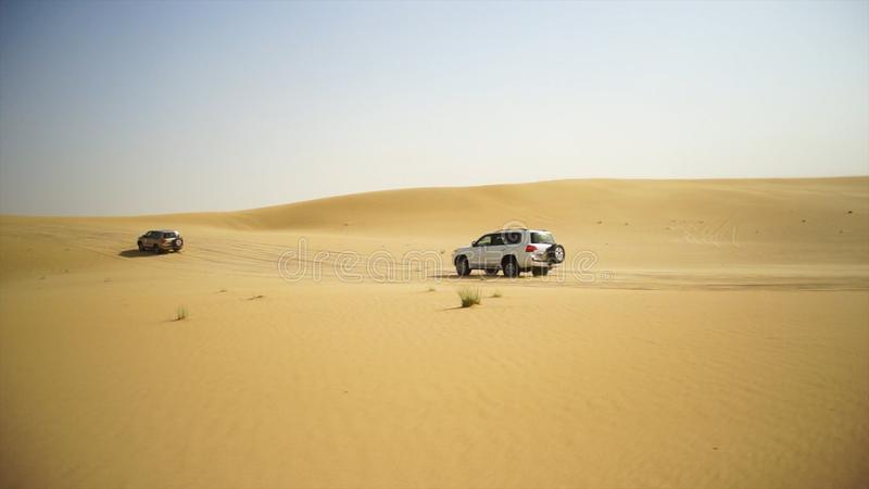 Abbandoni il safari SUVs che colpisce attraverso le dune di sabbia arabe Giro di SUV attraverso il deserto arabo fotografia stock