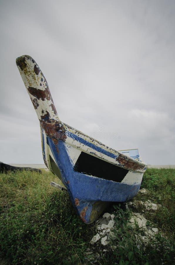Abbandoni la barca blu della fibra incagliata sulla riva con le nuvole molli e drammatiche fotografie stock libere da diritti
