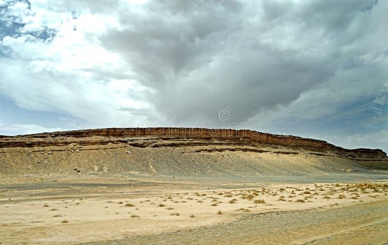 Abbandoni la roccia nelle montagne di atlante con le nuvole minacciose grige di pioggia nel Marocco fotografia stock libera da diritti
