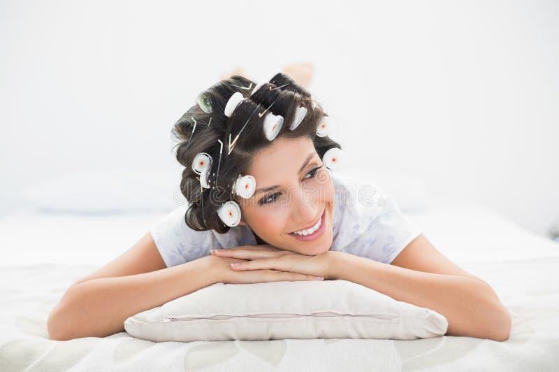 Abbastanza castana in rulli dei capelli che si trovano sul suo letto immagine stock