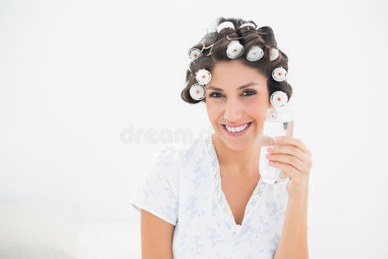 Abbastanza castana in rulli dei capelli che tengono bicchiere d'acqua a sorridente fotografie stock