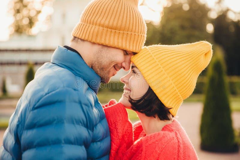 Abbastanza femminile castana ha tempo indimenticabile con il suo ragazzo, sguardo ad a vicenda occhi del ` s, sorride felicemente fotografia stock