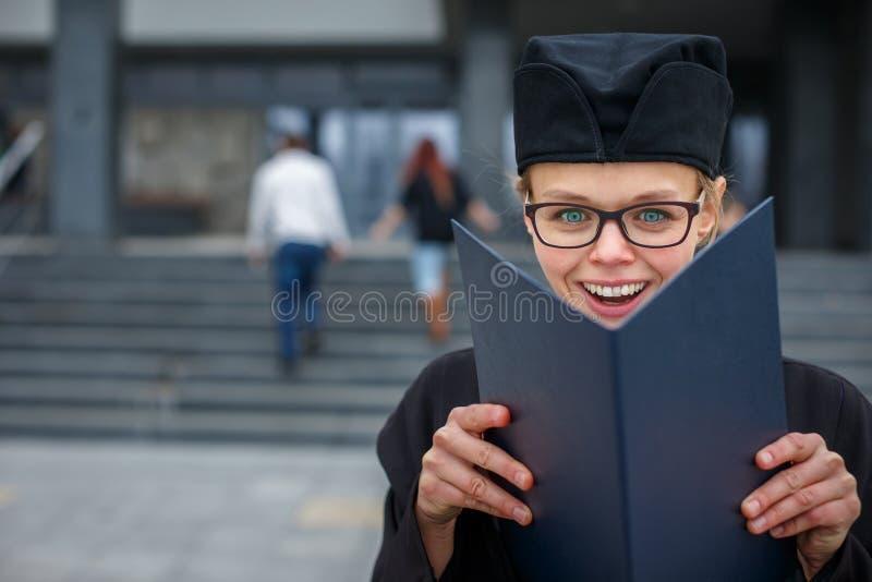 Abbastanza, giovane donna che celebra allegro la sua graduazione fotografia stock libera da diritti