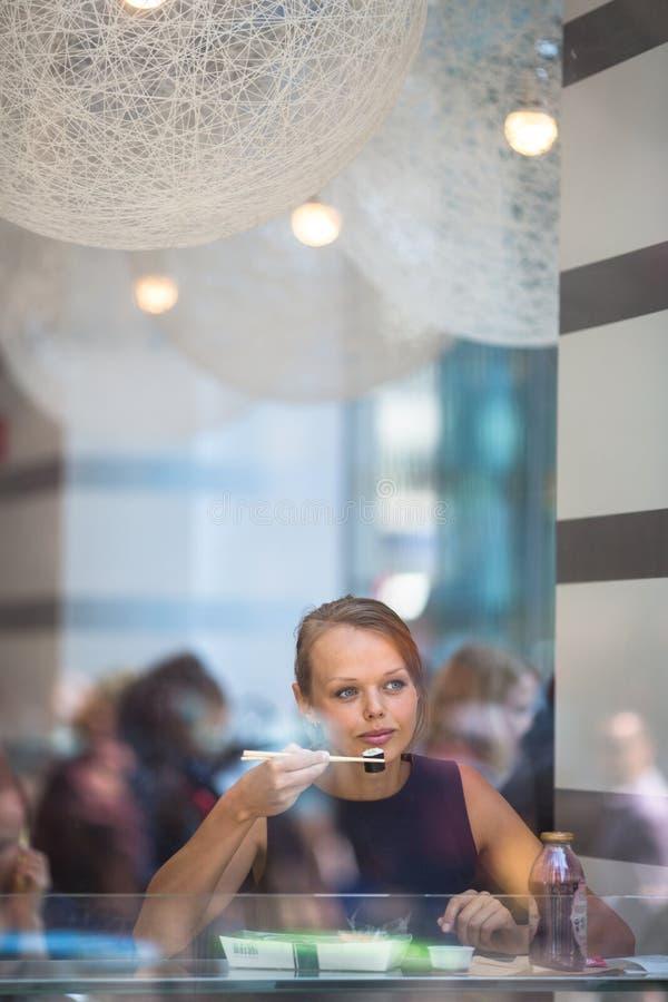 Abbastanza, giovane donna che mangia i sushi in un ristorante fotografia stock
