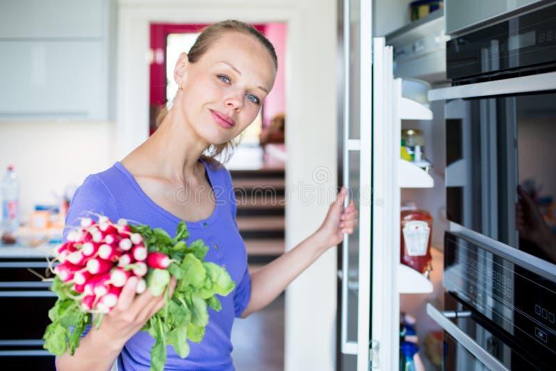 Abbastanza, giovane donna che prende gli ortaggi freschi dal suo frigorifero fotografie stock libere da diritti