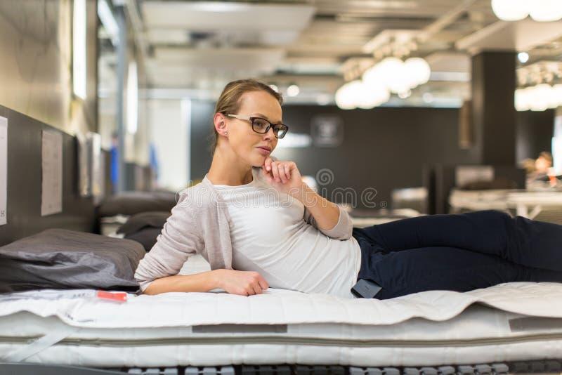 Abbastanza, giovane donna che sceglie il letto/mattrase giusti fotografie stock