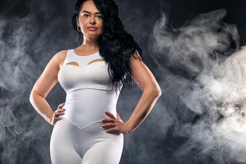 Abbastanza grassottello, dimensione più la donna che posa sul fondo nero nella palestra di forma fisica immagine stock libera da diritti