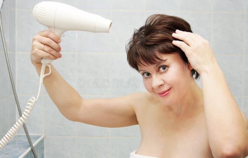 Abbastanza la donna invecchiata mezzo asciuga i suoi capelli con il hairdryer fotografia stock