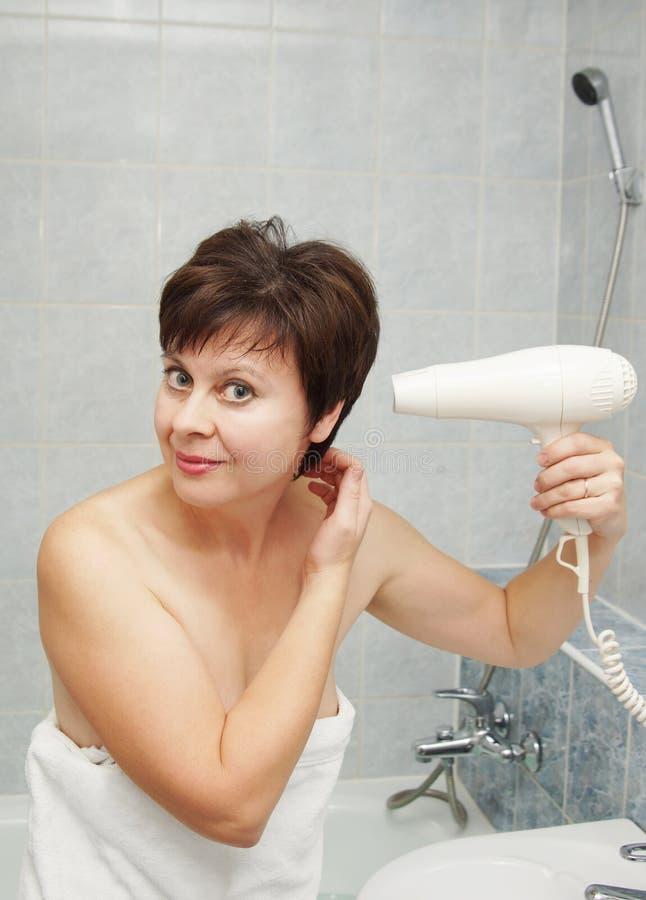 Abbastanza la donna invecchiata mezzo asciuga i suoi capelli nel bagno fotografia stock