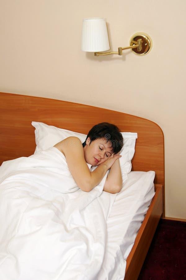 Abbastanza la donna invecchiata mezzo dorme in un letto immagine stock libera da diritti