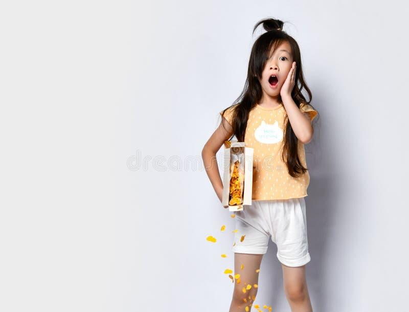 Abbastanza poco bambino asiatico della ragazza in vestiti domestici durante i supporti della prima colazione con i fiocchi di mai fotografia stock libera da diritti