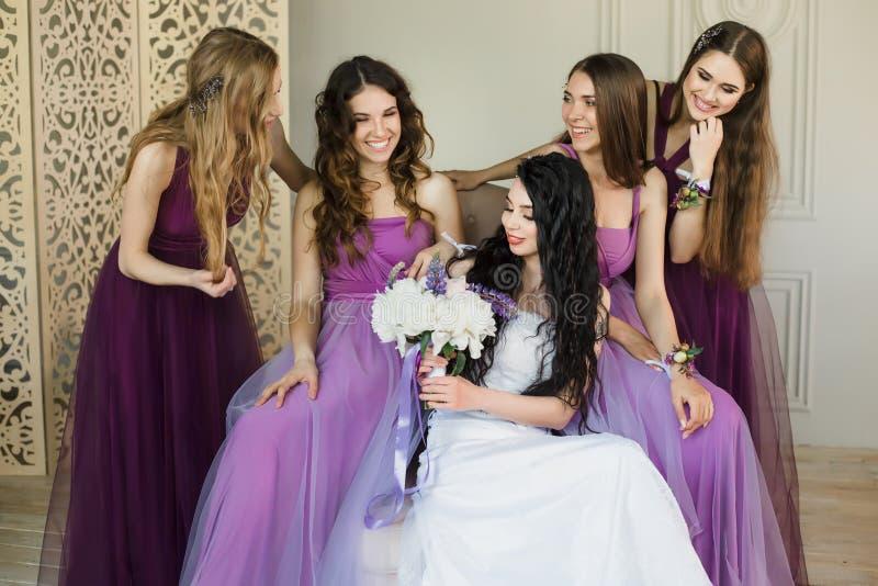 Abbattimento eccitato circa nozze Giovane sposa attraente che tiene un mazzo di nozze e che sorride mentre parlando con lei immagini stock