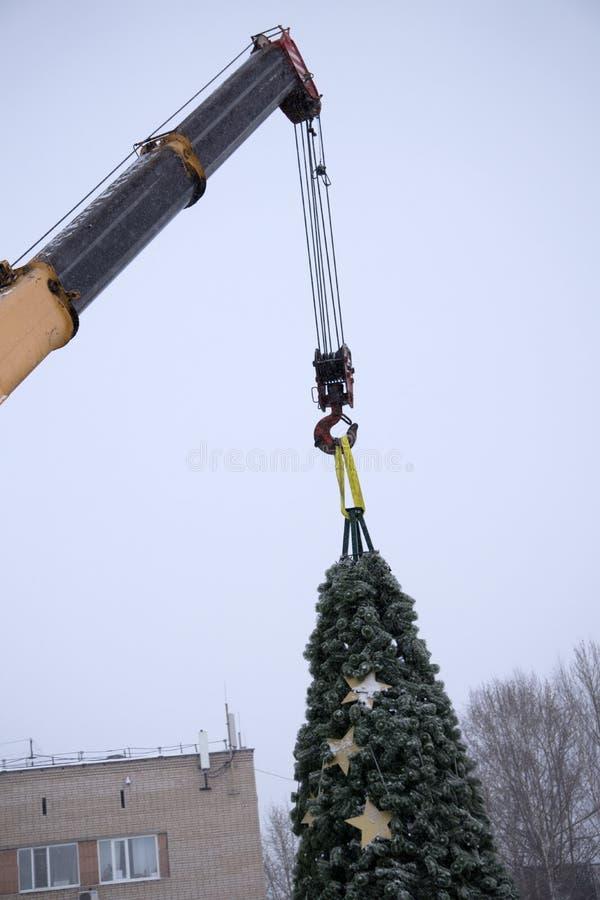 Abbau des Weihnachtsbaums mit einem Maschinenkranarbeiten lizenzfreies stockfoto