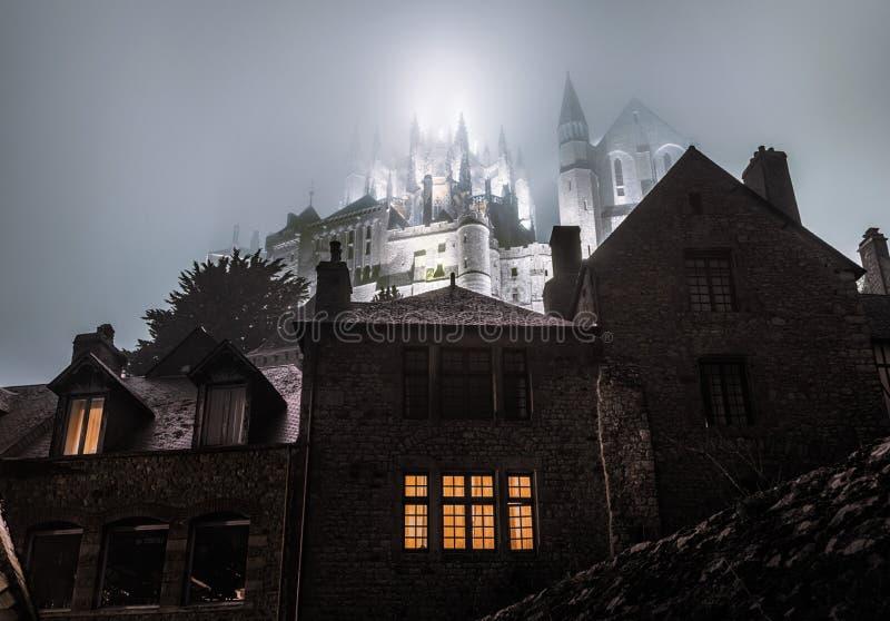 Abbazia nebbiosa del Saint Michel illuminata nella notte fotografie stock libere da diritti