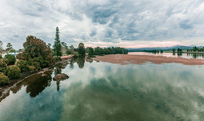Abbellisca con gli alberi, il lago ed i cieli dell'annuvolamento al crepuscolo immagine stock