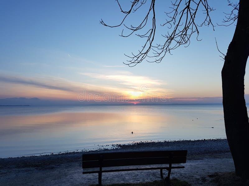 abbellisca con la siluetta di un banco per osservare il tramonto dalla riva di un lago fotografia stock libera da diritti