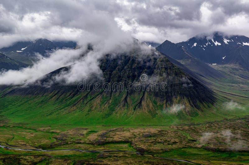 Abbellisca con le colline coperte dalle nuvole in Islanda ad ovest immagini stock
