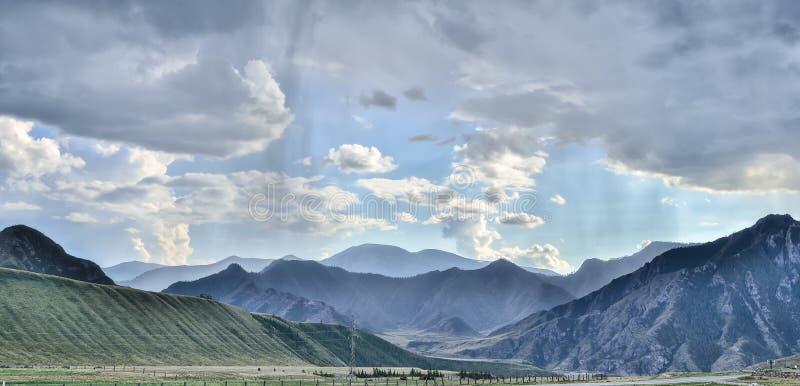 Abbellisca con pioggia e luce solare nelle montagne immagini stock libere da diritti